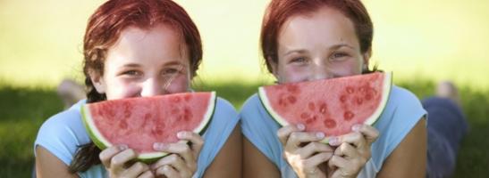 Slika dviju mladih djevojki s kriškama lubenice pokraj svojih lica. Ova slika ilustrira kako prateći savjete o tome kako se dobro osjećati će vam pomoći da raditi svoje omiljene stvari za vrijeme mjesečnice.