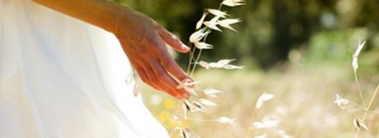 Slika žene koja stoji na polju. Slika ilustrira kako radimo za održivom razvoju i zaštiti okoliša.