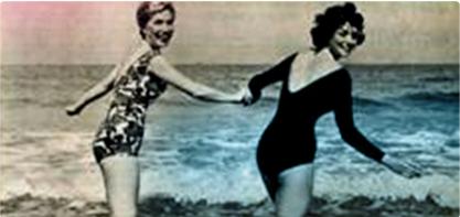 Slika dviju žena u kupaćim kostimima koje se drže za ruke. Slika je staromodna i prikazuje žensku revoluciju.