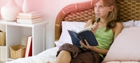 Slika mlade djevojke koja sjedi na krevetu i piše bilješke. Slika pokazuje kako postoji mnogo pitanja oko prve menstruacije ali ništa oko čega se treba brinuti!
