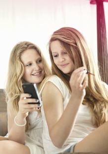 Slika prikazuje dvije mlade žene. Jedna drži mobitel a druga lakira nokte. Slika ilustrira kako su promjene koje se događaju u tijelu normalne te o njima možeš pričati s prijateljima ili roditeljima.